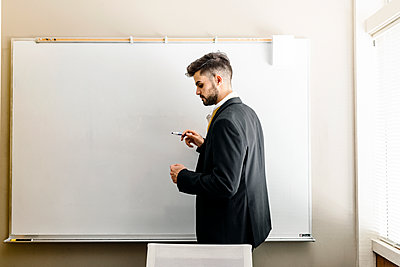 Man thinking with a marker on hand by white board at office - p1166m2095183 by Cavan Images