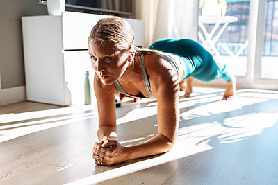 Woman practicing plank position while doing workout at home - p300m2256008 by Josep Suria