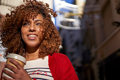 Afro woman with disposable coffee cup looking away while standing outdoors - p300m2257351 by Veam