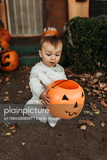 Adorable toddler boy dressed up as mummy on Halloween Trick-or-Treat - p1166m2208391 by Cavan Images
