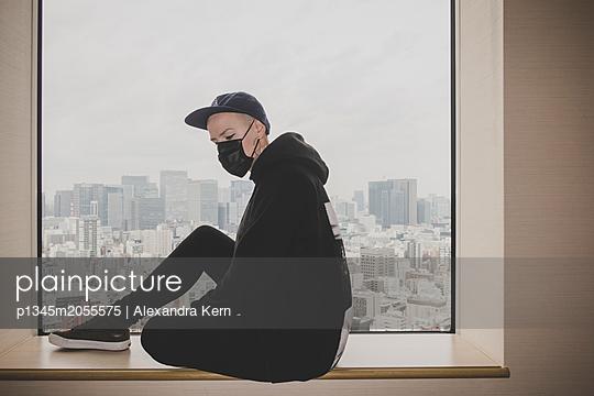 Frau sitzt auf dem Fensterbrett - p1345m2055575 von Alexandra Kern