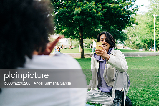 Young man photographing woman through smart phone at park - p300m2293266 by Angel Santana Garcia