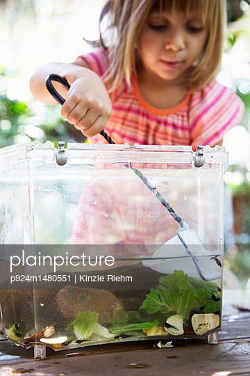 Girl scooping fishing net in plastic tadpole pond on garden table - p924m1480551 by Kinzie Riehm