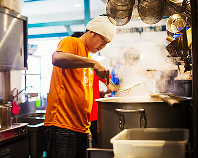 The ramen noodle shop. Staff preparing food in a steam filled kitchen.  - p1100m1185675 by Mint Images
