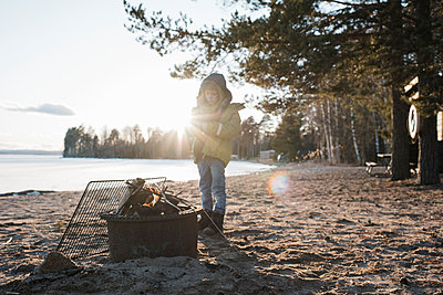 young boy stood next to a fire on the beach in Sweden - p1166m2171474 by Cavan Images