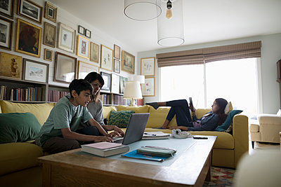 Mother and son using laptop and tween daughter using digital tablet on sofa - p1192m2000305 by Hero Images