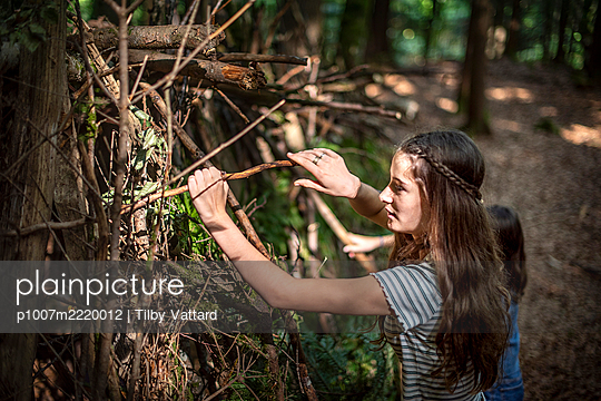 Two girls building a hut in the forest - p1007m2220012 by Tilby Vattard
