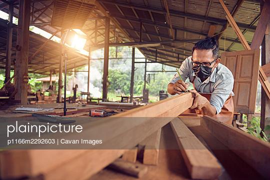 Closeup of a man carpenter using a nail gun.Carpenter using air  - p1166m2292603 by Cavan Images
