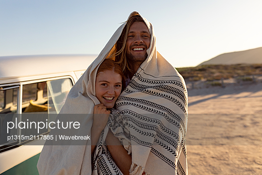 Happy couple wrapped in blanket near camper van at beach - p1315m2117885 by Wavebreak