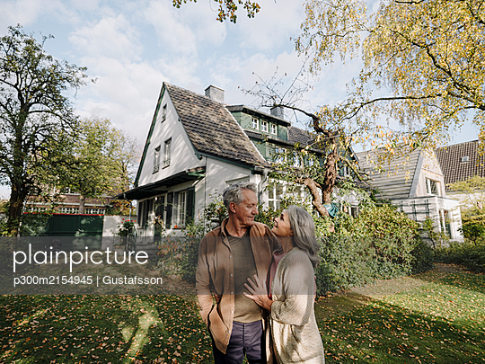 Senior couple in garden of their home in autumn - p300m2154945 by Gustafsson