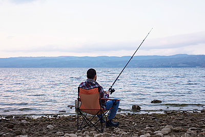 man in camp near lake, try to fishing - p1166m2124391 by Cavan Images