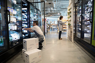 Male worker restocking refrigerated case in grocery store - p1192m1567216 by Hero Images