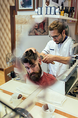 Barber cutting hair of a customer - p300m1081481f by Marco Govel