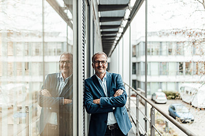 Smiling male entrepreneur with arms crossed leaning on window in office balcony - p300m2266304 by Gustafsson