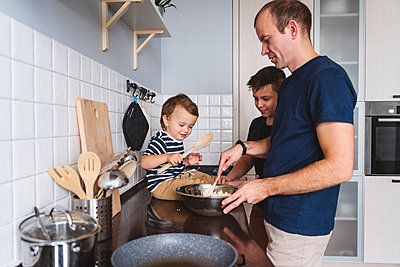 Father with cute sons preparing food in kitchen at home - p300m2277683 by Katharina und Ekaterina