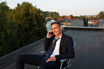 Geschäftsmann mit Smartphone auf dem Dach - p341m2008635 von Mikesch