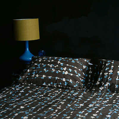 Double bed with patterned bed linen and dark painted walls - p349m695255 by Emma Lee