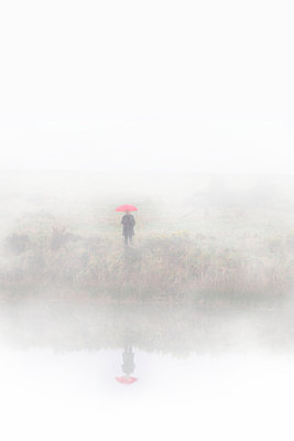 Woman standing at edge of lake holding red umbrella - p597m2063515 by Tim Robinson