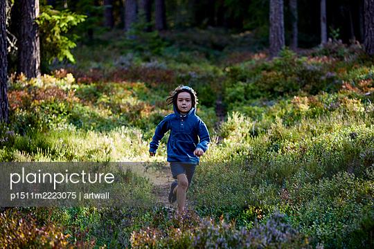 Junge läuft über eine Lichtung im Wald - p1511m2223075 von artwall