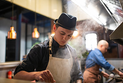 Young chef preparing food in kitchen - p1166m2250611 by Cavan Images