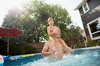 Playful father carrying son on shoulders in sunny swimming pool - p1192m1183988 by Hero Images