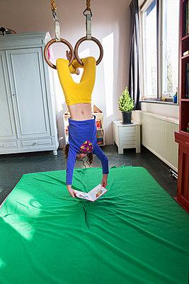 Girl reading upside down - p1231m2013518 by Iris Loonen
