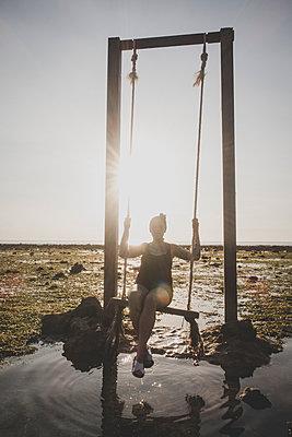 Frau auf Schaukel am Meer - p1345m2055629 von Alexandra Kern