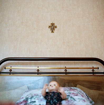 Doll placed on bed with crucifix on wall - p1468m1558911 by Philippe Leroux