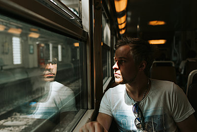 Young man on the train - p1507m2168047 by Emma Grann