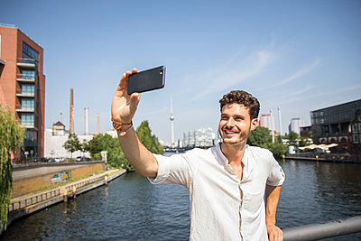man takes selfie on bridge in Berlin - p276m2110599 by plainpicture