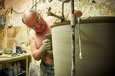 Potter in workshop working on large terracotta vase - p300m1191557 by Dirk Kittelberger