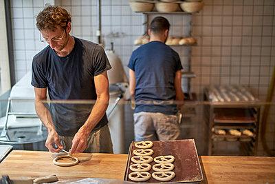 Bakers in bakery preparing fresh pretzls - p300m2005682 von Benjamin Egerland