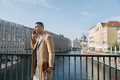 Businessman on the phone standing on a bridge, Berlin, Germany - p300m2143395 von Hernandez and Sorokina