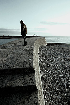 Man standing on the Cobb in Lyme Regis in Dorset - p3313106 by Gail Symes