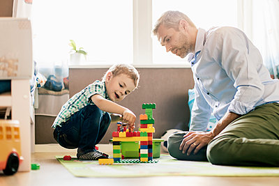 Father and son playing with toy blocks while sitting at home - p426m1179358 by Kentaroo Tryman