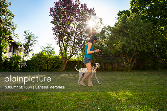 Girl with Dalmatian in the garden - p300m1587354 von Larissa Veronesi