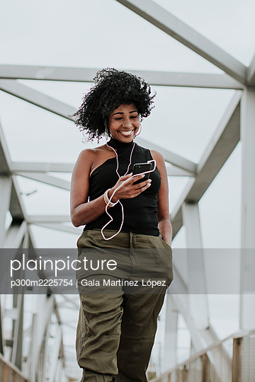 Smiling woman using smart phone listening to music through earphones standing on bridge in city - p300m2225754 by Gala Martínez López