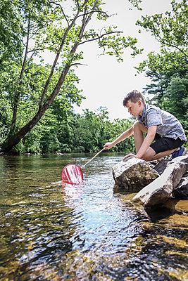 Boy on the riverbank holding spoon net - p1019m1462174 by Stephen Carroll