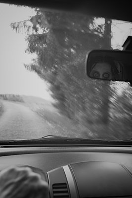 Man driving car while ghost watching him through rear view mirror - p300m1060674 by Miriam Dörr