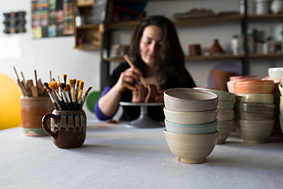 Potter shaping clay in her workshop, focus on foreground - p300m2118481 by Andrés Benitez