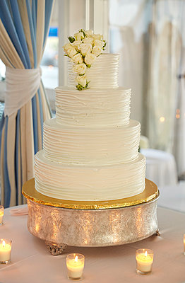 Multi-Tiered Wedding Cake with White Roses Surrounded by Candles - p694m2145290 by Maria K