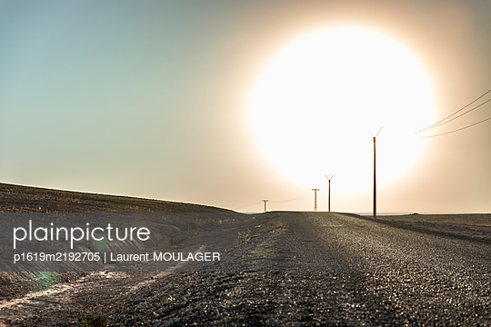 Bright sun burning a Moroccan road in the Agafay desert near Marrakech - p1619m2192705 by Laurent MOULAGER