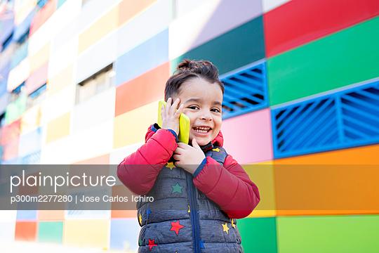 Happy boy talking smart phone by wall - p300m2277280 by Jose Carlos Ichiro