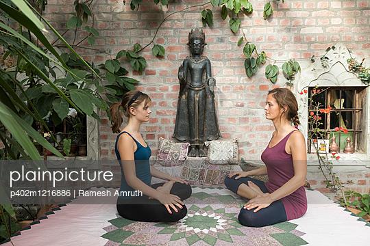Mutter und Tochter, Yoga im Wintergarten - p402m1216886 von Ramesh Amruth