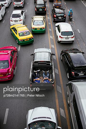 Schlafende Menschen auf der Transportfläche eines Pickup Trucks - p728m2141765 von Peter Nitsch