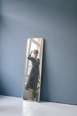 Young woman in vintage dress looking into mirror - p300m2023589 von Joseffson