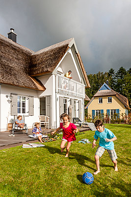 Happy brother and sister playing football in garden - p300m2143566 by Ega Birk