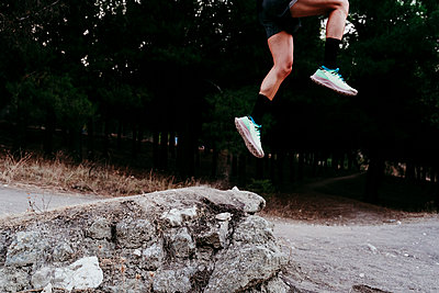 Young male athlete jumping over rock at mountain - p300m2251165 by Eva Blanco
