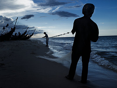 Two silhouetted men tend to a fishing net extending from a fishing boat pulled up on shore, Dong Hoi, Quang Binh Province, Vietnam, Southeast Asia - p934m892997 by Boris Zuliani