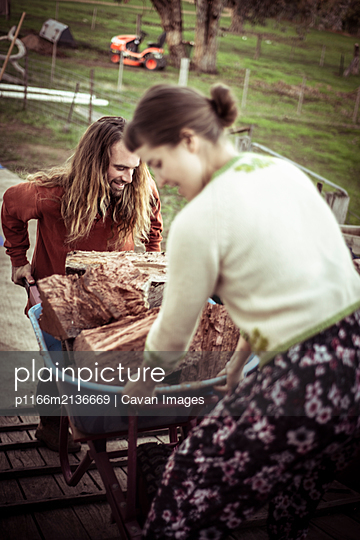 young couple man and woman stack wood in wheelbarrow on farm - p1166m2136669 by Cavan Images